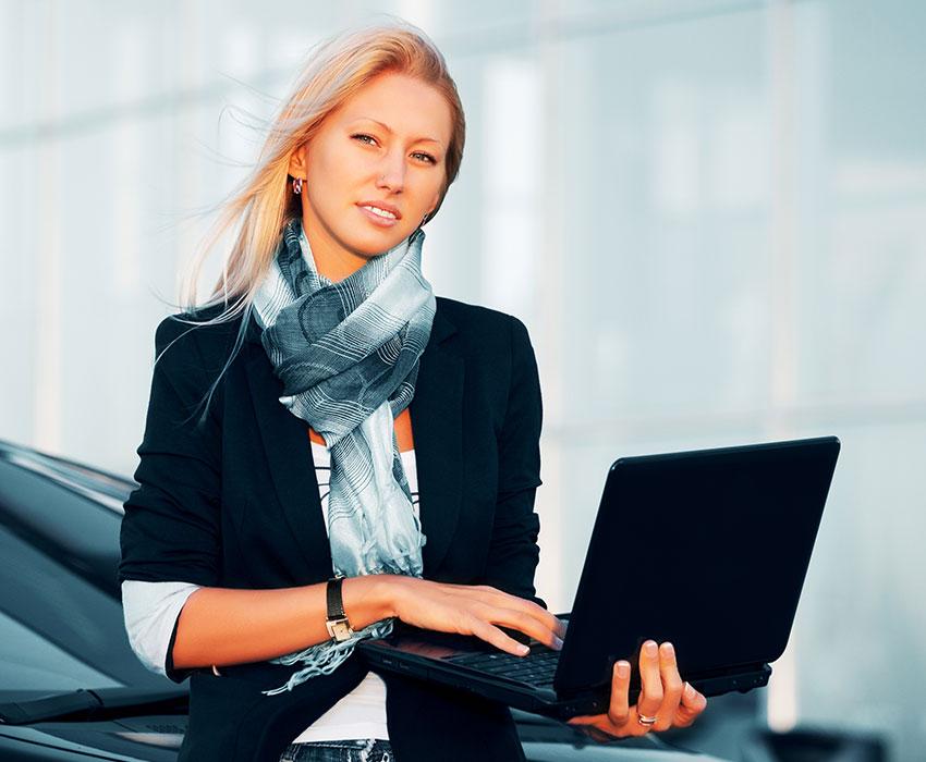 Blonde Frau die am Auto lehnt und ein Laptop hält
