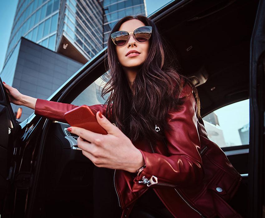 Junge brünette Frau mit Sonnenbrillet steigt aus Ihrem LeaseForce Leasingauto