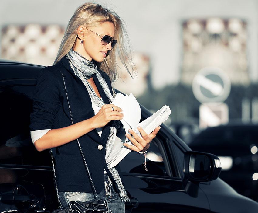 Junge blonde Frau vor Auto mit einem Stapel Unterlagen