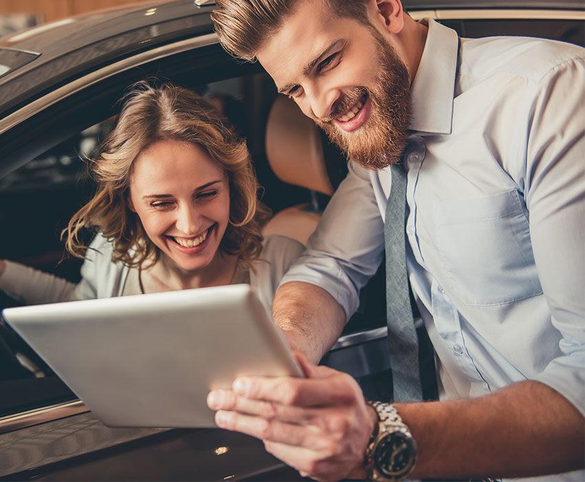 Junger Mann und junge Frau bei Übergabe eines Leasingwagens