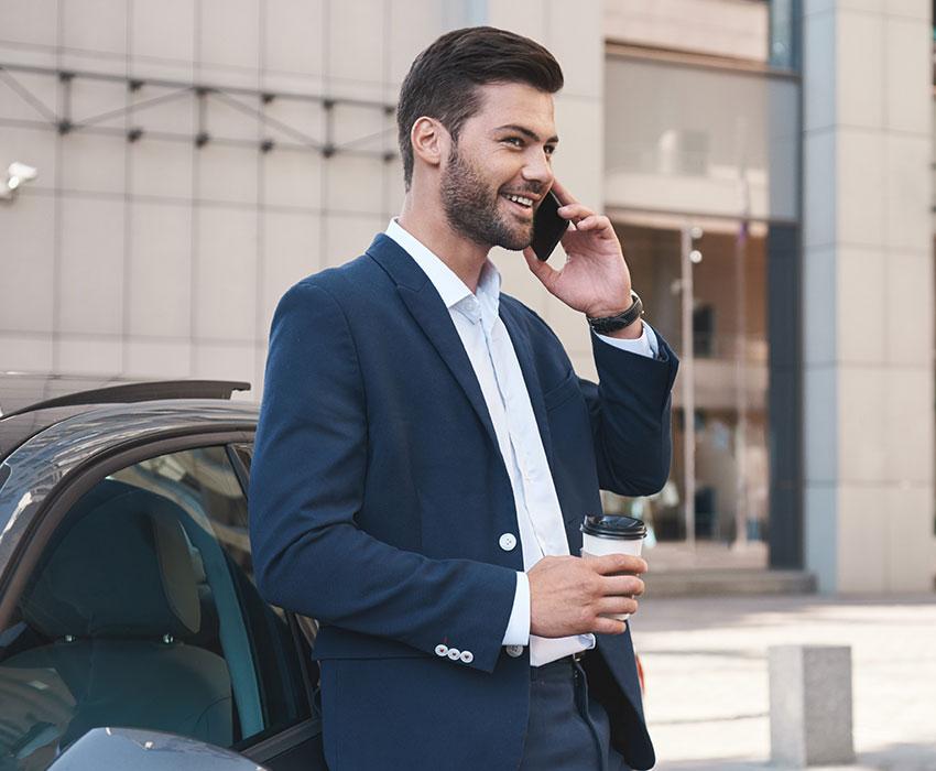 Businessmann im Anzug der angelehnt an ein Auto telefoniert