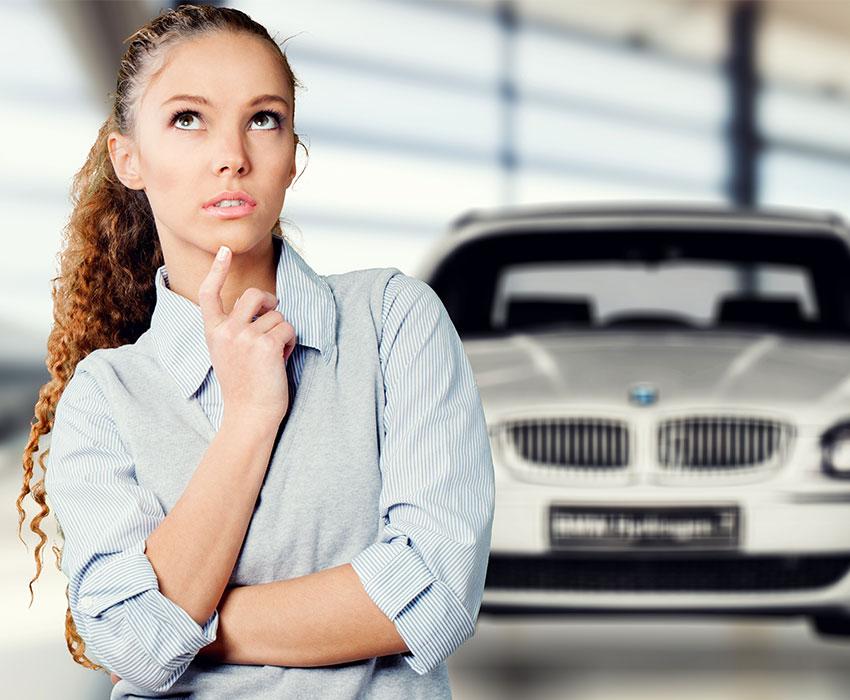 Junge Frau die überlegend vor einem BMW steht
