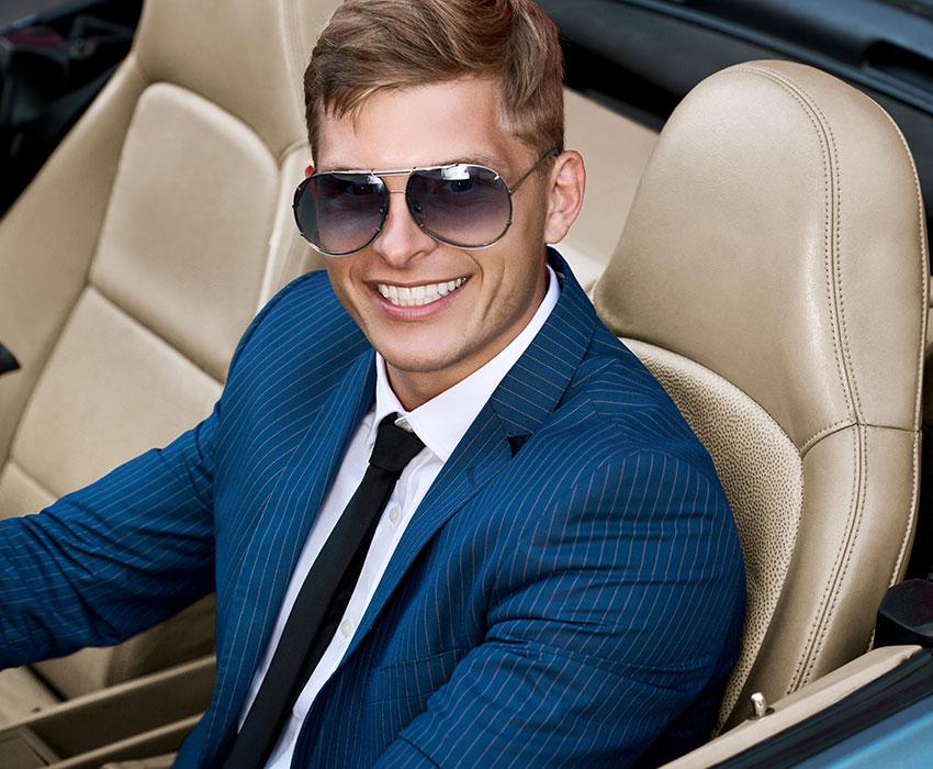 Businessmann mit Sonnenbrille im geleasten Auto