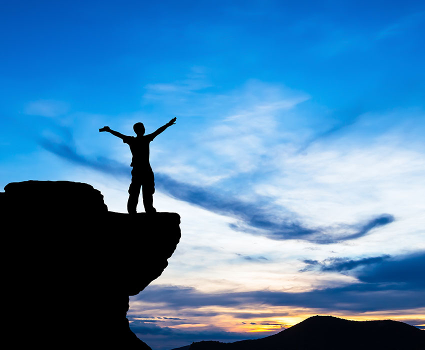 Mann der mit ausgebreiteten Armen auf einem Berg steht