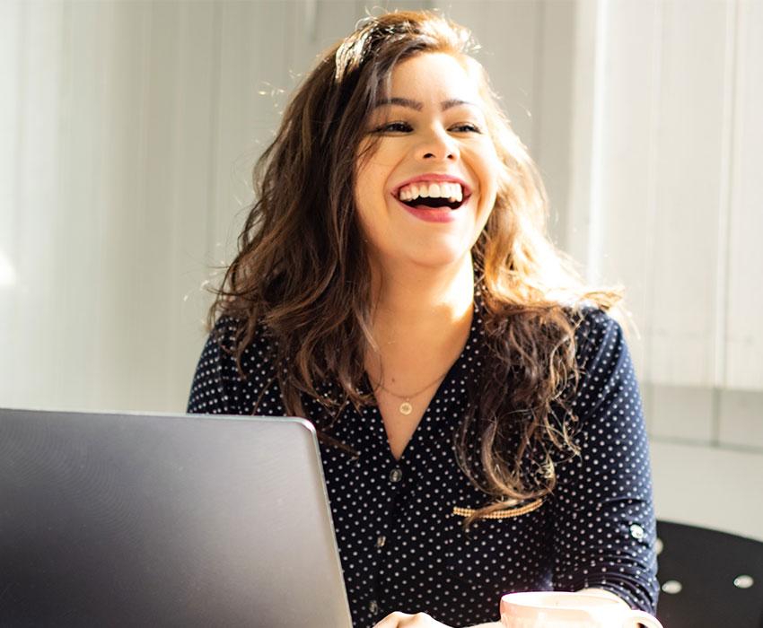 Brünette Frau die vor dem Laptop sitzt und sich freut