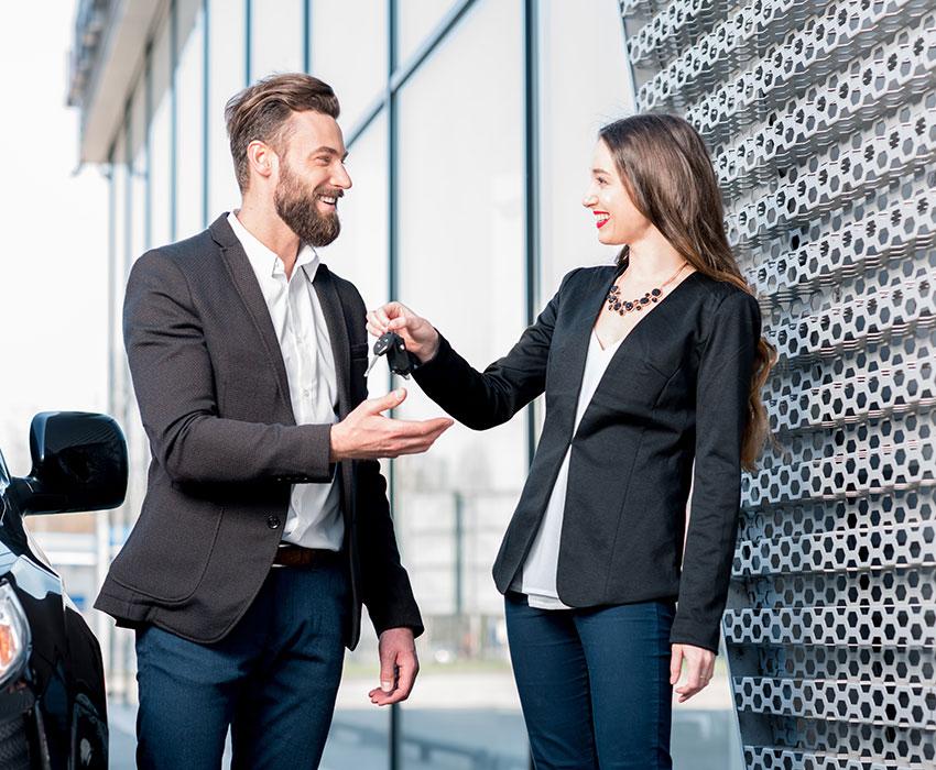 Junge Frau übergibt Schlüssel für Leasingauto an Businessmann