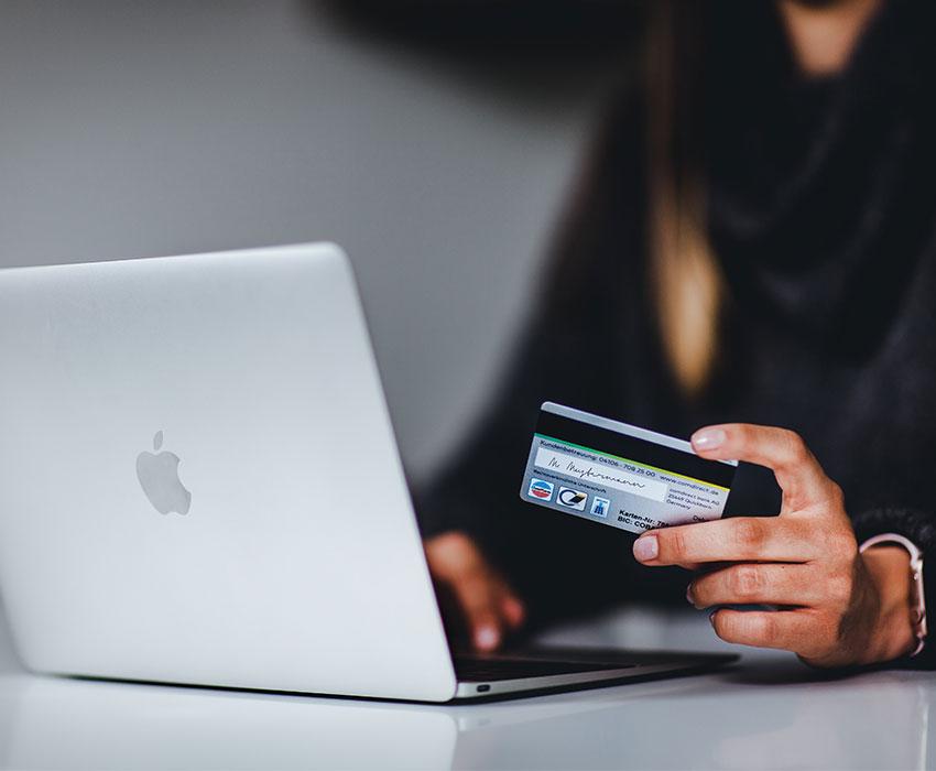 Frau die Kreditkarte hält vor dem Laptop sitzt